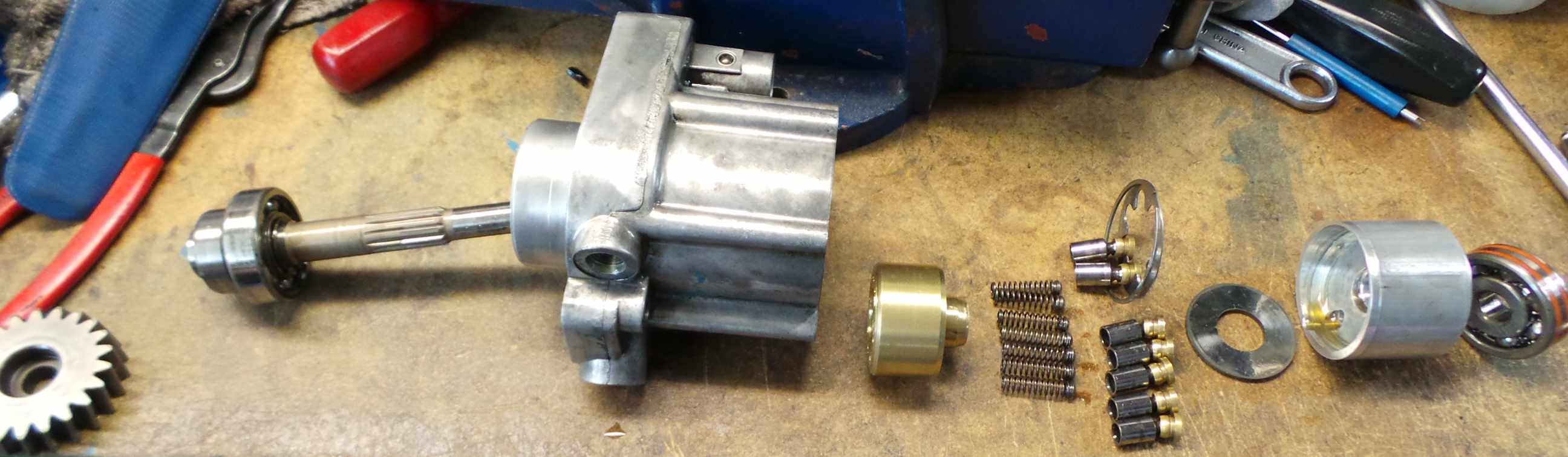 Above: Left to right: Gear, Shaft, Main bearing, pump housing with steal  valve seat still inside, brass cylinder core, piston springs, pistons, ...